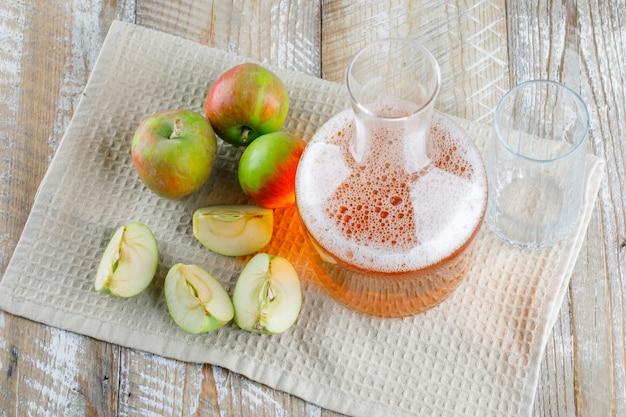 Äpfel mit saft auf holz- und küchentuch