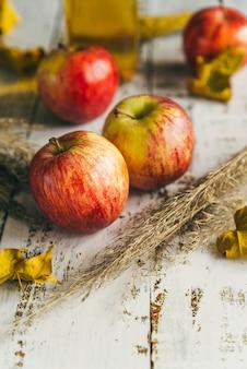 Äpfel mit trockenen blättern auf schäbiger tabelle