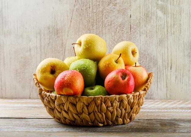 Äpfel mit tropfen in einem weidenkorb auf hellem holz und grunge
