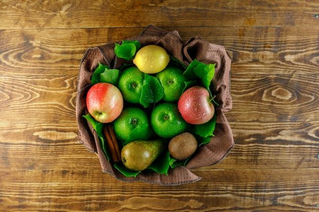 Äpfel mit zitrone, birne, kiwi, zimtstangen, blätter auf holztisch
