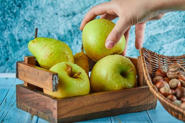 Äpfel und birne in holzkorb und schüssel haselnüsse auf blauem tisch.