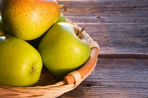 Äpfel und birnen in einem korb auf einem holztisch