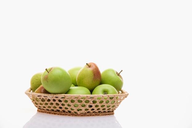 Äpfel und birnen in einem korb auf einem weißen hintergrund