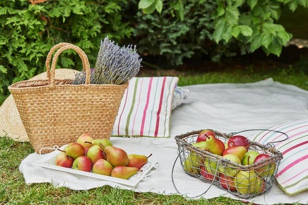 Äpfel und birnen in einem korb auf grünem gras im sommer