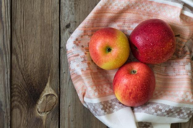 Äpfel und birnen liegen auf einem naturholztisch auf einem handtuch. speicherplatz kopieren