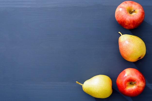 Äpfel und birnen säumten die ecke auf einem grauen hölzernen hintergrund mit copyspace