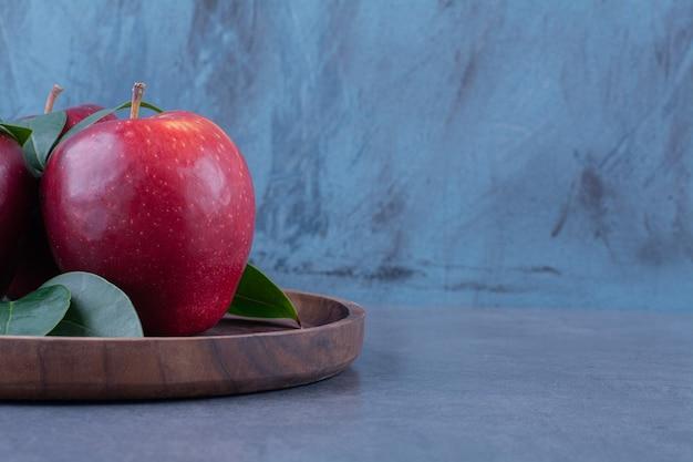 Äpfel und blätter auf dem brett auf der dunklen oberfläche