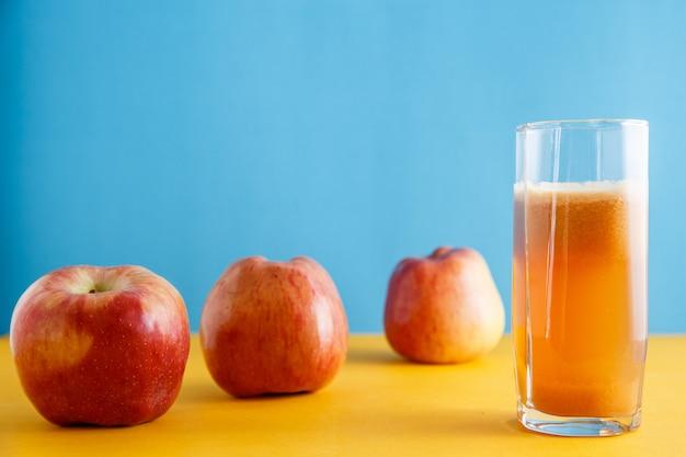 Äpfel und ein glas natürlicher apfelsaft auf gelbblau