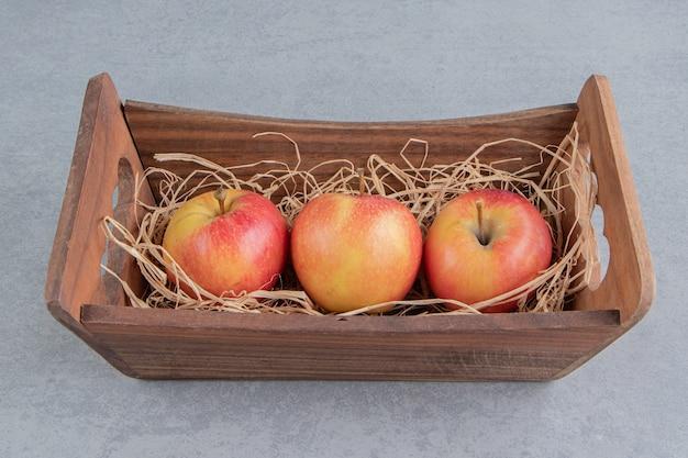Äpfel und ein strohhaufen in einem holzkorb auf marmor