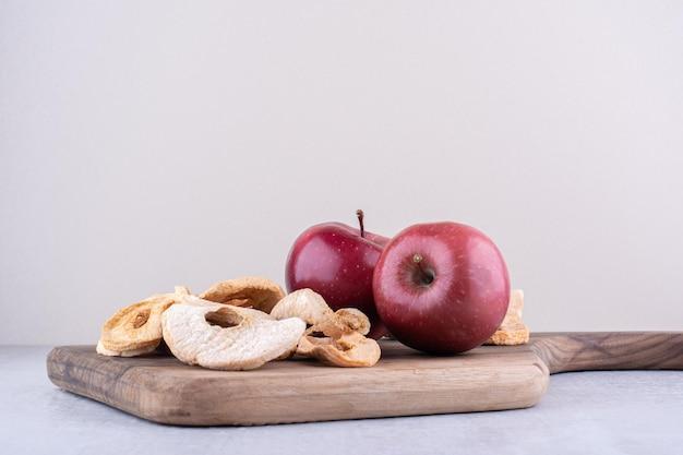 Äpfel und getrocknete apfelscheiben auf einem brett auf weißer oberfläche