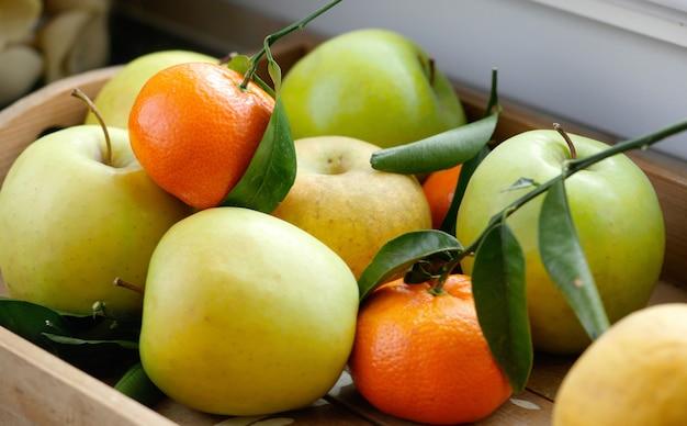Äpfel und mandarinen in holztablett