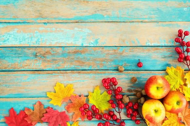 Äpfel und rote beere auf holztisch über ahornblättern
