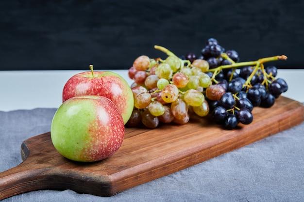 Äpfel und trauben auf einem holzbrett.