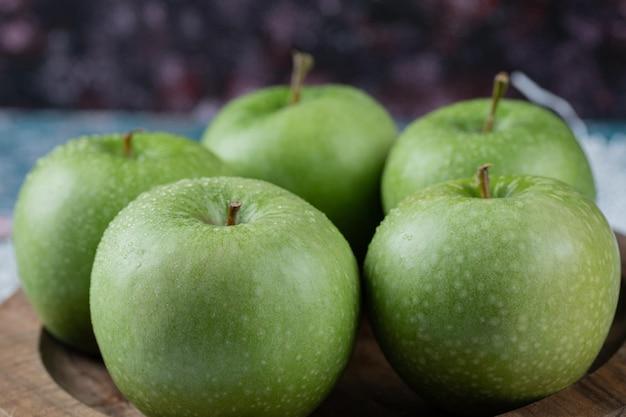 Äpfel werden auf runder holzplatte serviert.