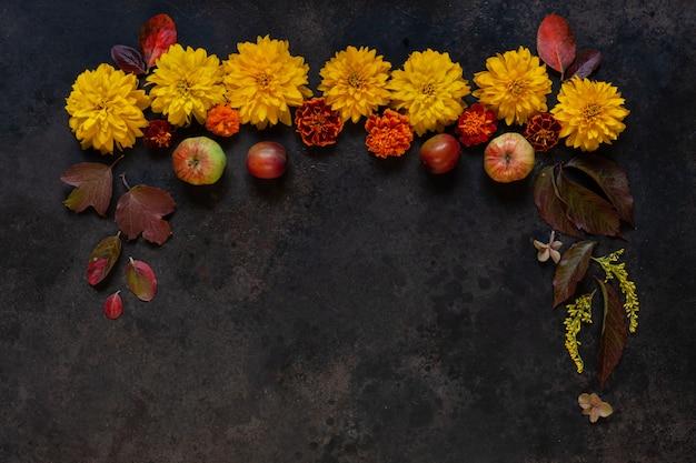 Äpfel, wilde kirschpflaumen, rote beeren und schöne herbstblumen mit blumenschmuck des kopienraumes.