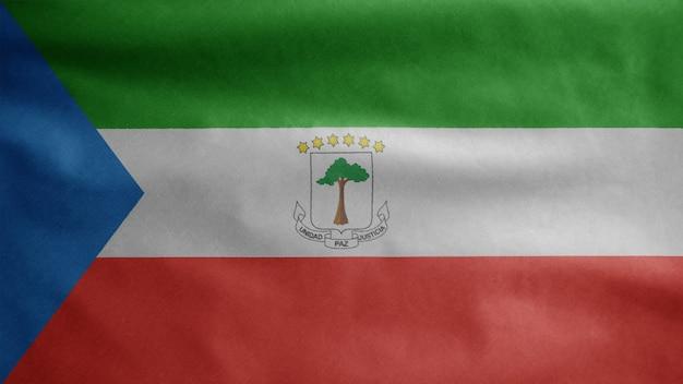 Äquatoguineische flagge weht im wind. nahaufnahme von äquatorialguinea banner weht, weiche und glatte seide. stoff textur fähnrich hintergrund. verwenden sie es für das konzept für nationalfeiertage und länderfeiern