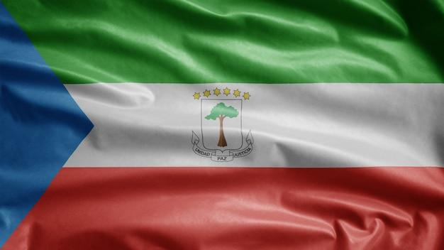 Äquatoguineische flagge weht im wind. nahaufnahme von äquatorialguinea banner weht, weiche und glatte seide. stoff textur fähnrich hintergrund