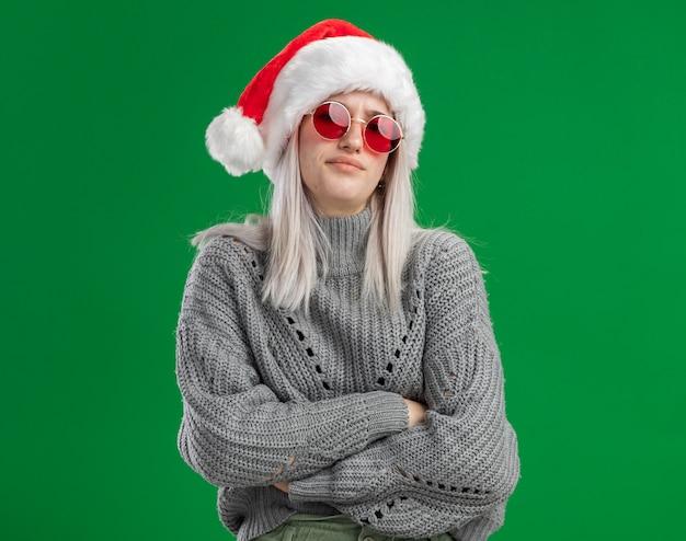 Ärgerliche junge blonde frau im winterpullover und in der weihnachtsmannmütze, die rote brille betrachten kamera mit stirnrunzelndem gesicht mit verschränkten armen stehen über grünem hintergrund