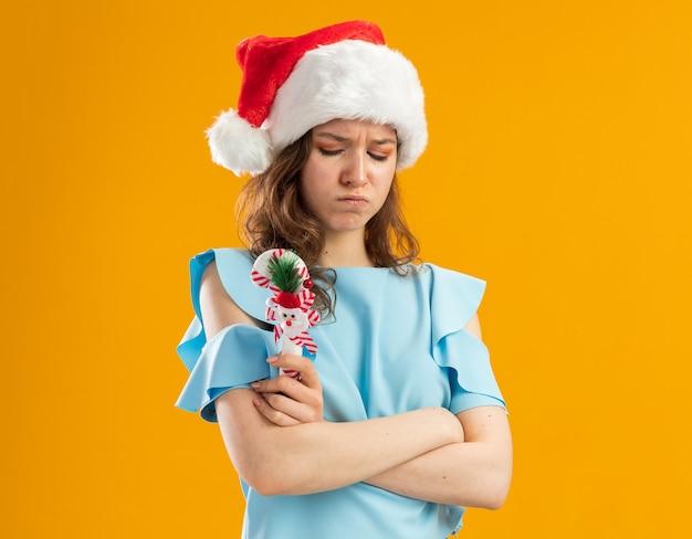 Ärgerliche junge frau in der blauen spitze und in der weihnachtsmannmütze, die weihnachtszuckerstange mit verschränkten armen die stirn runzelt