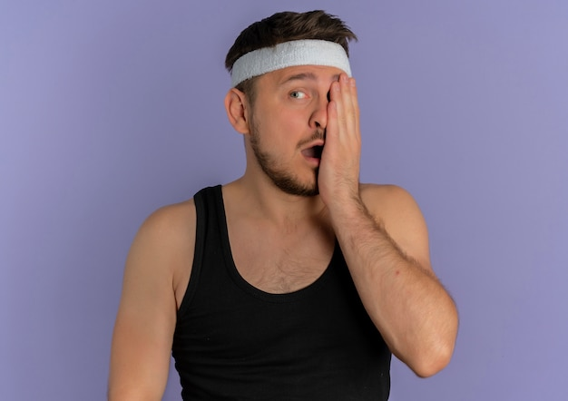 Ärgerlicher junger fitnessmann mit stirnband, das ein auge mit arm über lila hintergrund abdeckt
