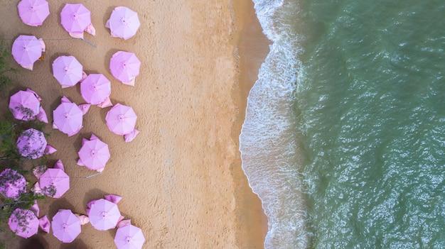 Aerial draufsicht auf den sandstrand. rosafarbene regenschirme.