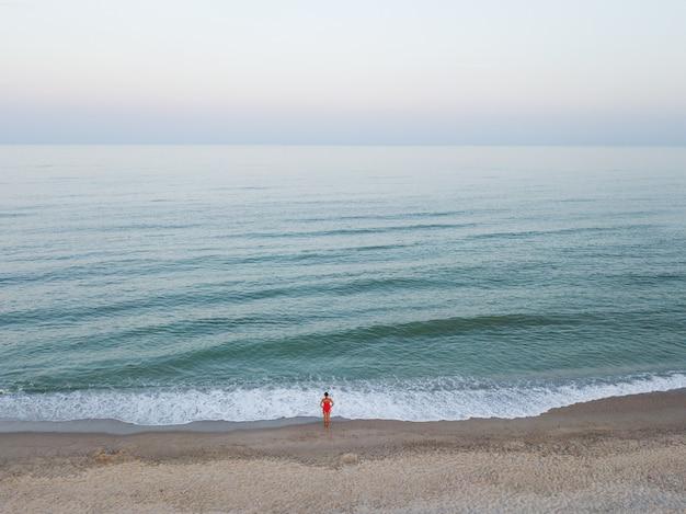 Aerial draufsicht auf frau im roten bikini in der nähe von meer am strand