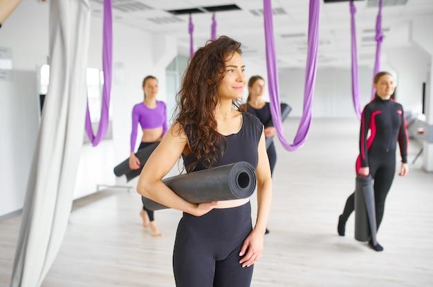 Aerial oder fly yoga studio, gruppentraining, hängematten hängen. fitness, pilates und tanzübungen mischen sich. frauen auf yogi-training im fitnessstudio, passen lebensstil