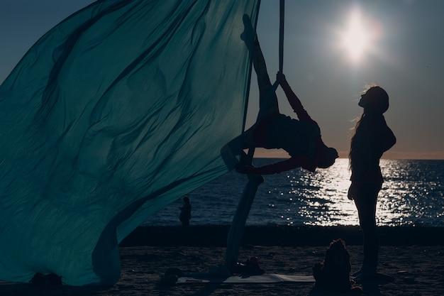 Aerial yoga am strand. gesunde frau.