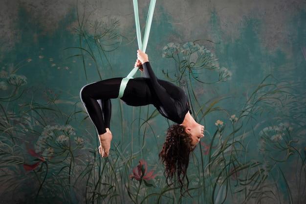 Aero yoga eine junge frau, die yoga macht oder sich an einer aufhängung dehnt