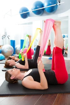 Aerobic pilates frauen mit gummibändern in einer reihe