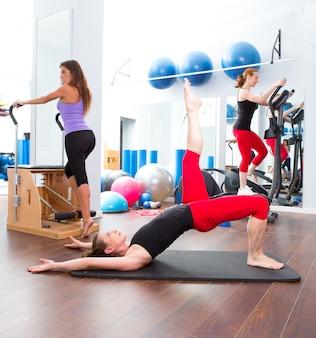 Aerobic pilates-gymnastikfrauengruppe und crosstrainer