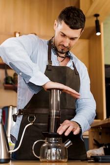 Aeropress-kaffee: barista-presse auf gerät drücken und kaffeetropfen gießen aeropress in die kanne