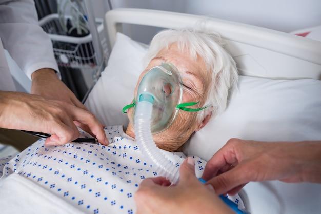Ärzte, die ältere patienten mit stethoskop untersuchen