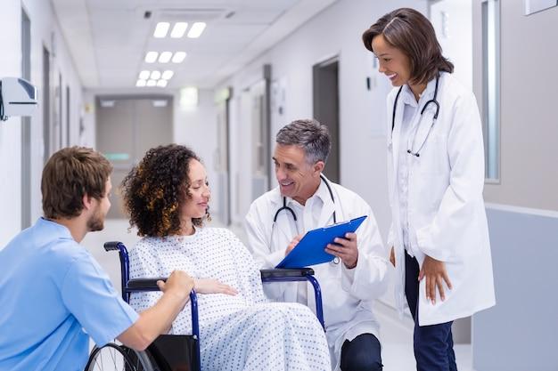 Ärzte, die mit der schwangeren frau im korridor interagieren
