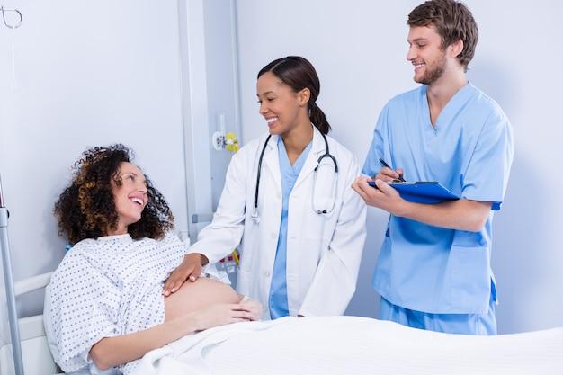 Ärzte, die mit der schwangeren frau in der station interagieren