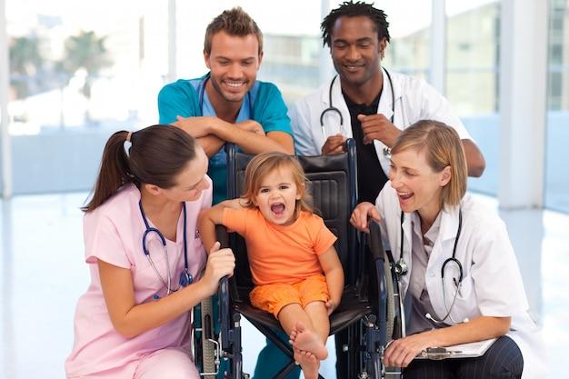 Ärzte, die mit einem baby in einem rollstuhl spielen