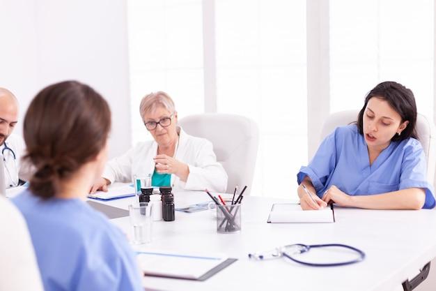 Ärzte, die während der teambesprechung ein medizinisches gespräch mit ihren mitarbeitern führen. klinikexperte, der mit kollegen über krankheiten spricht, mediziner.