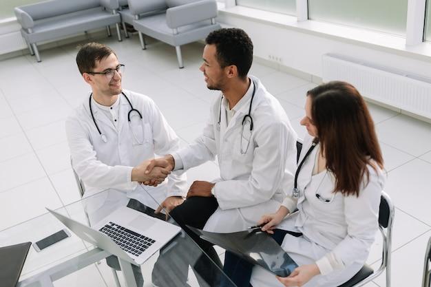 Ärzte diskutieren die krankengeschichte des patienten in einem arbeitstreffen.