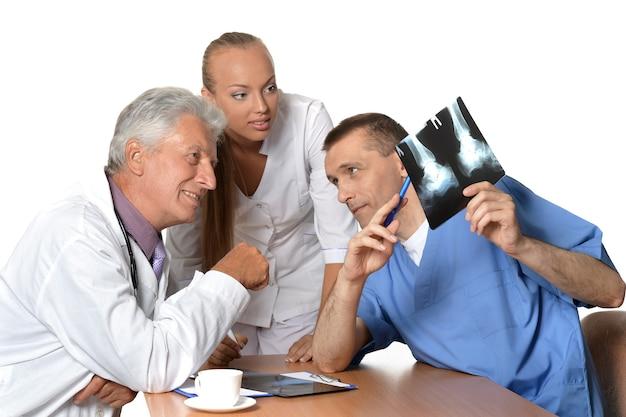 Ärzte diskutieren röntgenaufnahmen am tisch auf weißem hintergrund