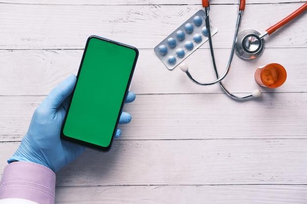 Ärzte geben schutzhandschuhe mit einem smartphone ab
