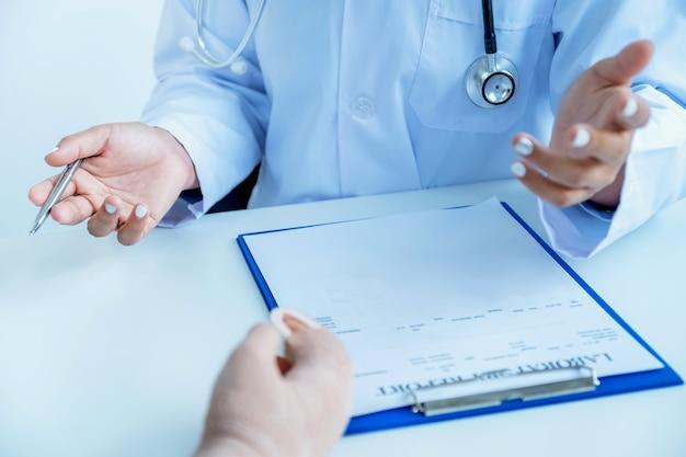 Ärzte halten einen stift in der hand und berichten über die ergebnisse der gesundheitsuntersuchung, empfehlen den patienten medikamente