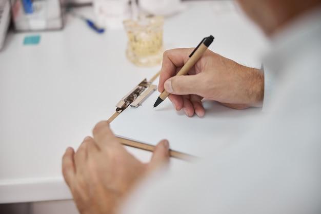 Ärzte halten einen stift in der hand und machen sich notizen auf einem leeren papier