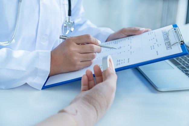 Ärzte halten einen stift in der hand und melden die ergebnisse der gesundheitsuntersuchung, empfehlen patienten bei einem armunfall medikamente.