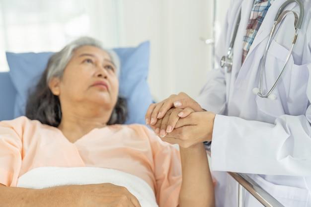 Ärzte halten hände, um ältere ältere patientinnen im krankenhaus-senioren-frauen-medizin- und gesundheitskonzept zu ermutigen