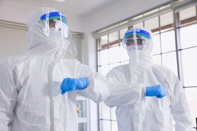 Ärzte in der laboranalyse und probenahme von covid-19-infektionskrankheiten. sie grüßen nach beendigung der guten arbeit.