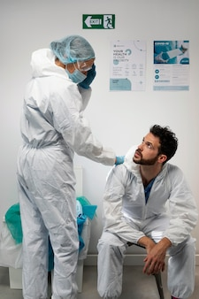 Ärzte in gefahrgutanzug mittlerer schuss
