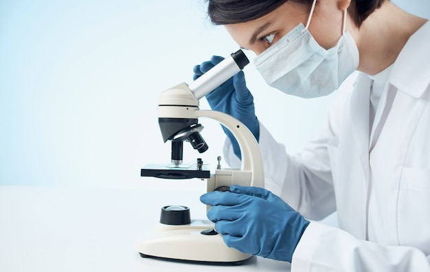 Ärzte in medizinischen handschuhen schauen durch ein mikroskop auf den tisch und den impfstoff gegen chemische elemente im labor. hochwertiges foto