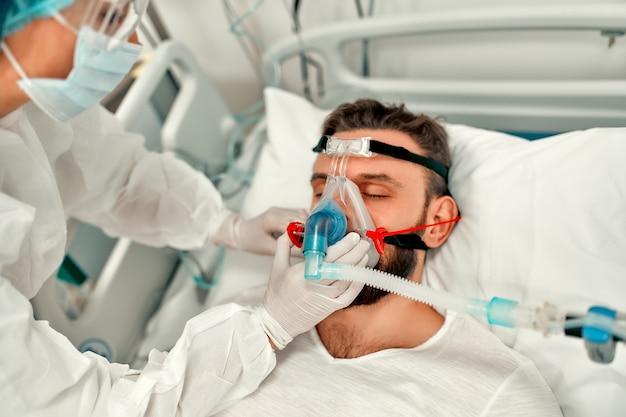 Ärzte in schutzanzügen und masken überwachen den zustand des patienten