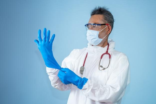 Ärzte in schutzkleidung aus gefahrstoff-psa tragen medizinische gummihandschuhe zum schutz der coronavirus-krankheit 2019 (covid-19).