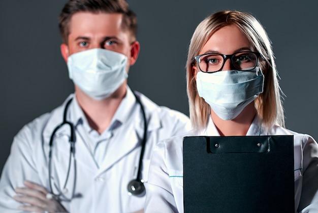 Ärzte in schutzmasken und handschuhen auf dunkelgrauem hintergrund